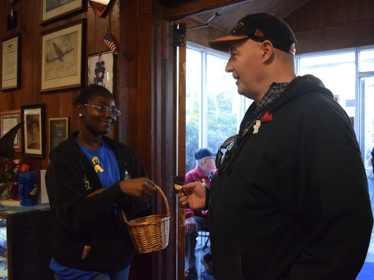 Timesha Harvey, 17, (left) gives a Veterans Day yellow