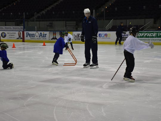 A volunteer coach for the Pensacola Junior Ice Flyers helps kids learn to skate during the USA Hockey sponsored Try Hockey For Free Day Saturday at the Bay Center.