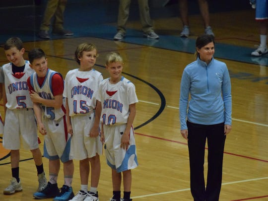 Middle School boys basketball coach Erin Gorman watches with members of the team as they are introduced.