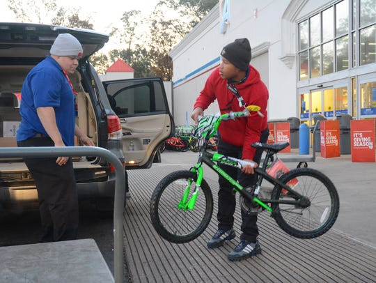 Academy + Outdoors employee T.J. Watts loads a bicycle for a customer visiting the Jackson store on Black Friday.