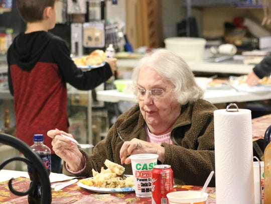 Bobbye Potts starts at her meal during the dinner at