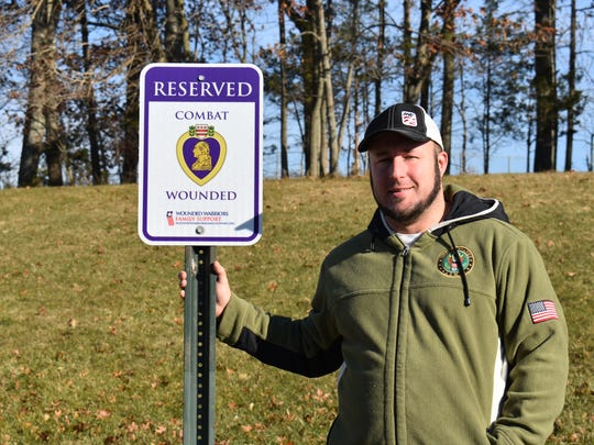 Justin Macarone of the Somerset section of Franklin next to one of two Combat Wounded designated parking space signs at RVCC.