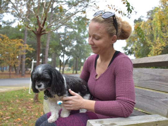 Mylania Wilson sits with her Shih Tzu, Sophie, on Thursday at the Gulf Breeze Disc Golf Park.