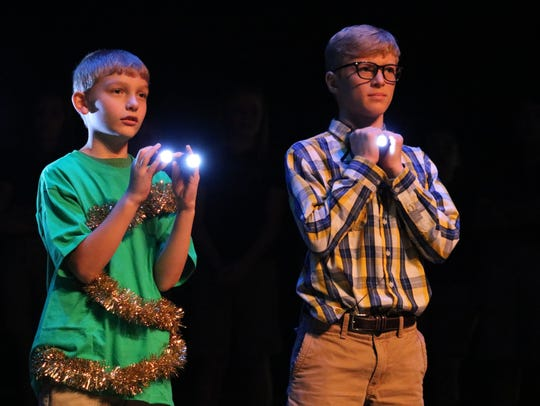 "Ethan Byrd and Trayce Eckman hold up lights to show that ""Jesus is the light of the world"" as part of the Christmas play."