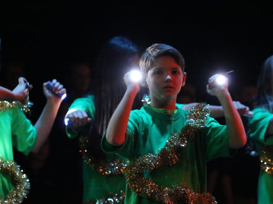 """Lane Clements poses with lights as part of the """"light of the world"""" performance."""