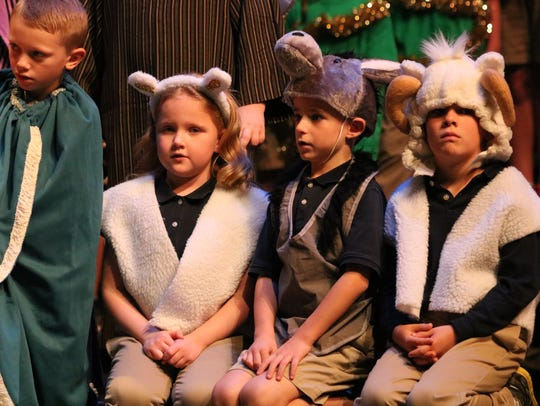 Sarah Peak, Gage Wozencraft, and Isaac Buckman sit on the ground as the animals at the manger.