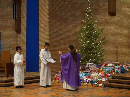 Rev. Zoy Garibay is pictured blessing the Angel Tree gifts before delivery.