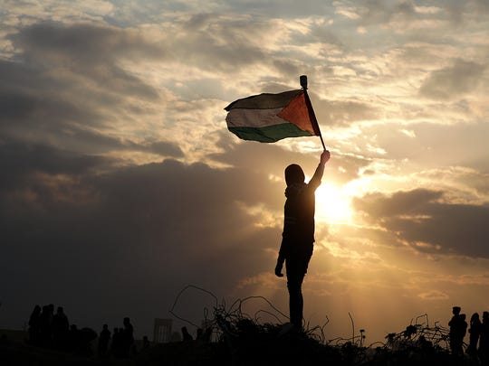 A Palestinian protester holds up a Palestinian flag
