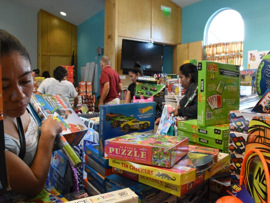 Families pick out gifts for their children inside the