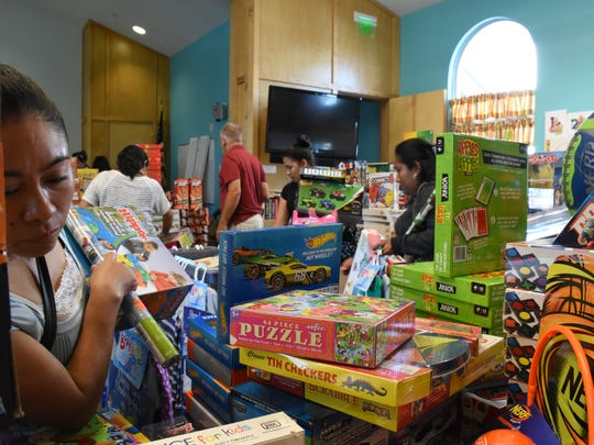 Families pick out gifts for their children inside the Christmas store at Grace Place for Children and Families on Dec. 19, 2017. Many families weren't able to afford toys post-Hurricane Irma, so Grace Place decided to step in to help provide about 800 children a Merry Christmas.