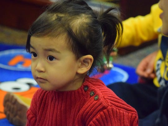 Joanna Lee listens intently as the toddlers are read