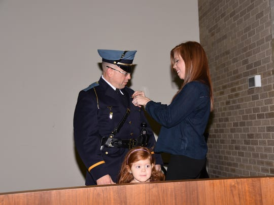Pedro Casiano was promoted to Vineland Police Captain during a recent  City Hall ceremony. His wife, Rachel Casiano, pins his badge, while his daughter, Jacquelyn, looks at the audience.