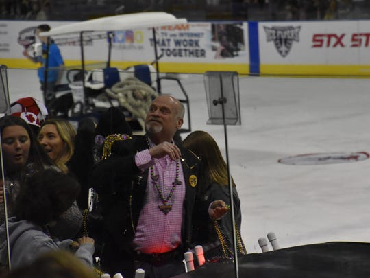 Pensacola Mardi Gras president Danny Zimmern tosses beads to crowd of 4,339 Saturday night at Bay Center for Ice Flyers game.