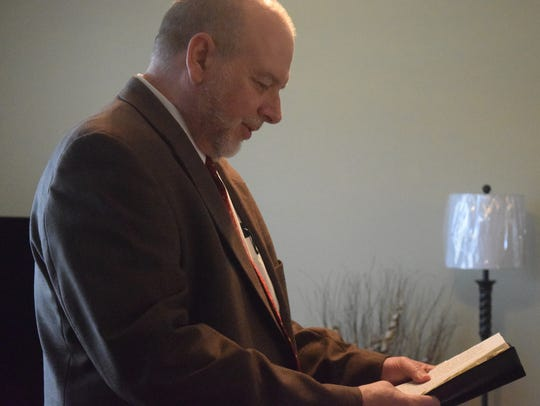 Pastor Ken McGeehee reads from the bible during the