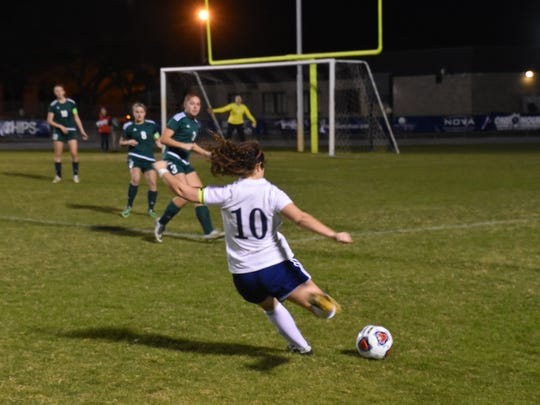 Gulf Breeze senior Rainey Niles blasts shot toward goal in the Dolphins 4-3 win against Choctaw for district tournament title.