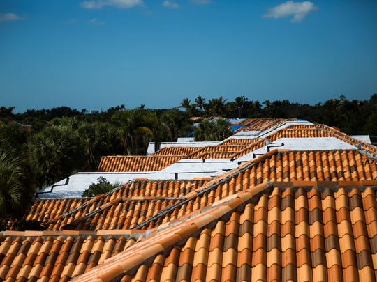 Roofs with tarps on Thursday, February 1, 2018 in the Village Walk community in North Naples. Roofing companies are doing roughly 10 times the normal number of jobs, following Hurricane Irma.