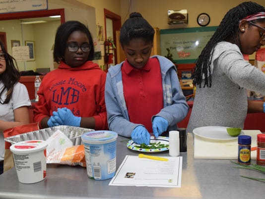 Viviana Martin (far left), Kyri Gordon, Janyah Clay and Madison Wilson, all member of the Garden and Nutrition Club at the Pineville Youth Center, prepare the ingredients which will be part of the seven-layer dip they are making for other members of the Pineville Youth Center. The Garden and Nutrition Club is part of the Good Food Project