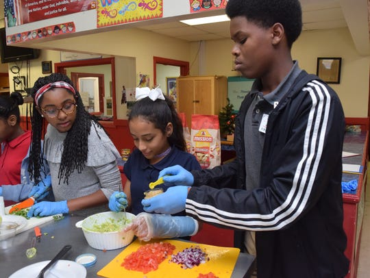 "Madison Wilson (left), Nayah Mayorca and Fredrick Nelson, all members of the Garden and Nutrition Club at the Pineville Youth Center, mix up the ingredients for a seven-layer dip they are making. The Garden and Nutrition Club is part of the Good Food Project. The members served up two heart healthy snacks on Valentines Day to other children at the center. ""Each week we do a healthy, nutritious snack with the kids,"" said Frances Boudreaux, director of the Good Food Project.  Boudreaux said the seven-layer dip is used to teach the club members about the five food groups.The club served the dip and cups of fruit, yogurt and granola."