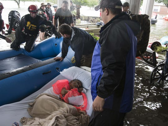 Rescuers, some trained first responders and others volunteers, help to evacuate the Gulf Health Care Center, a nursing home in Port Arthur, Texas. Elderly patients, many of the bedridden, needed assistance getting out of the facility that had nearly a foot of water in the lobby by 3 p.m. Wednesday.