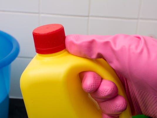 household chemical bottle in pink washing up glove
