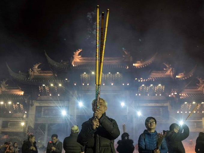 People pray with incense sticks to celebrate the Lunar