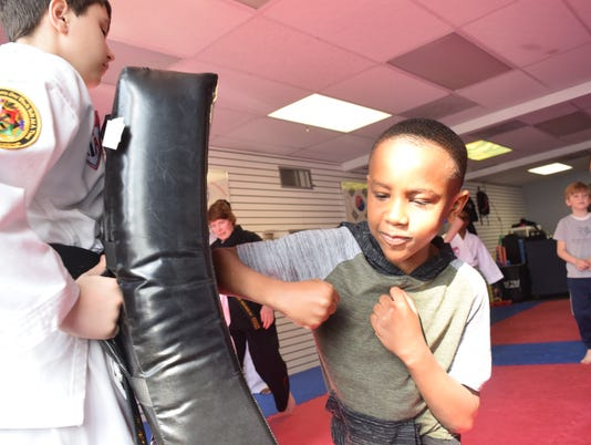 Jameson Gray (right) practices a self defense technique using his elbows on a pad held by by Joseph Sanroma while attending a free Safety Day class held at Master Rousseau's Taekwondo Saturday, Feb. 17, 2018. In the Safety Day children were taught how to identify strangers and what to do if the strangers approach them. Self-defense techniques were also taught. Officer Micheal Jones also spoke with the children about what to do when approached by strangers and about what constituents an emergency and when to call 911.