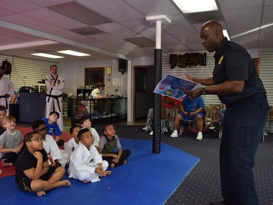 Officer Micheal Jones (right) spoke with the children about what to do when approached by strangers, what constituents an emergency and when to call 911 at a free Safety Day held Saturday at Master Rousseau's Taekwondo. Children were taught how to identify strangers and what to do if the strangers approach them. Self-defense techniques were also taught.