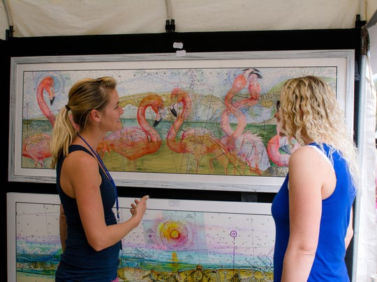 Personally showing the artwork to art patrons gave the festival an added plus, as pictured with the artist, at left, giving some perspective to an interested patron, at right.