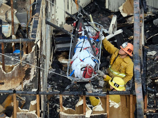 Firefighters guide a body being lifted by a ladder truck from the burned-out ruins of an abandoned office building in the Westlake district just west of downtown Los Angeles Tuesday, June 14, 2016.