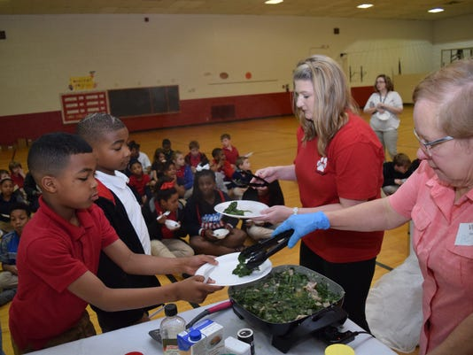 Lessie Moore Elementary third-graders Laronne Dirty (left) and Ja'Quon Holmes are served collard greens by P.E. teacher and garden sponsor Christy Parker (second from right) and Frances Boudreaux, executive director of the Good Food Project. The collard greens were recently harvested from the school's garden. Boudreaux was at the school to conduct a cooking demonstration with the collard greens.