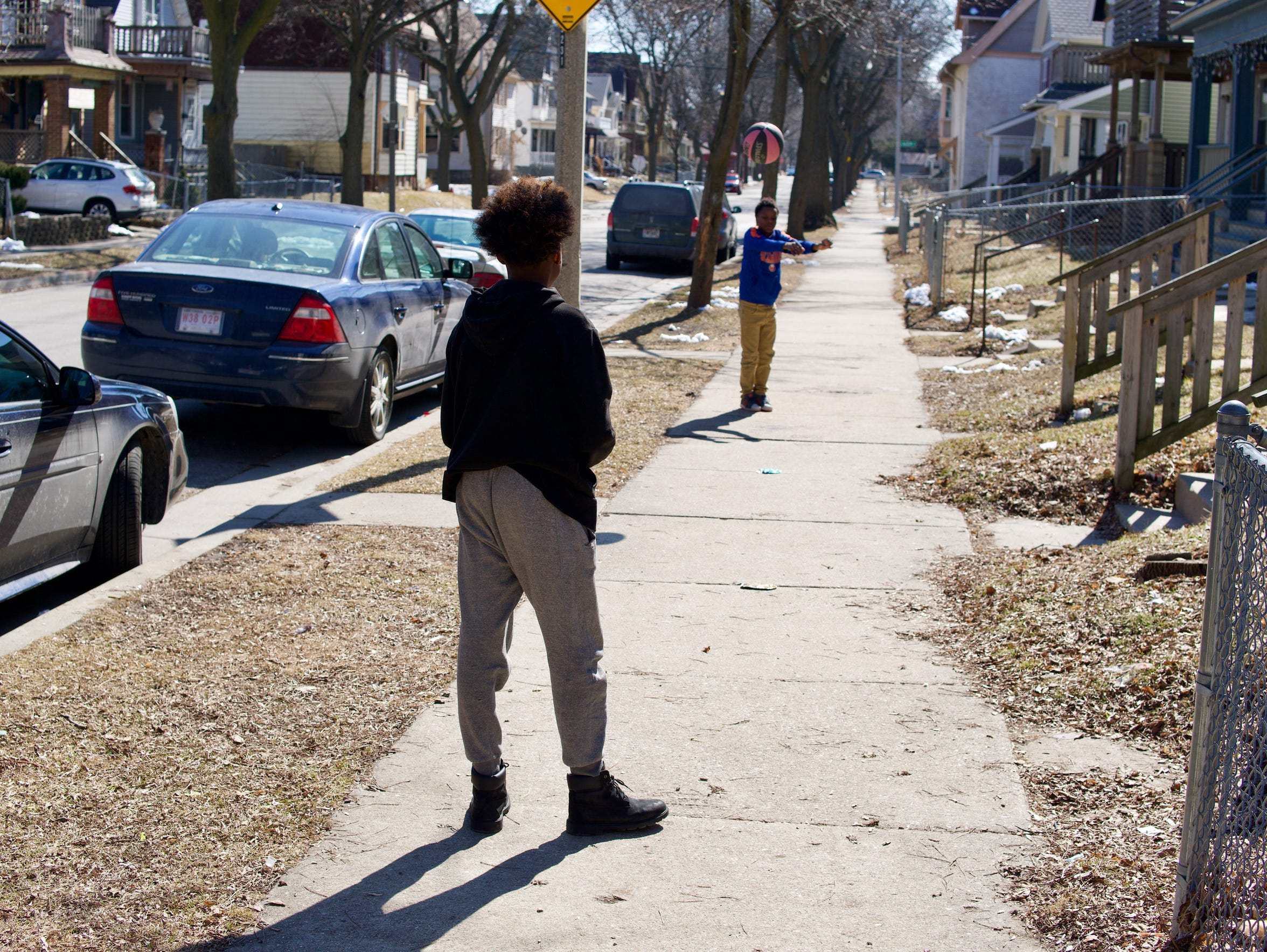 Teenagers bounce a basketball to one another on a cool Saturday afternoon across the street from a memorial to Demetrius A. Eason. Eason was shot to death in June 2017 in the 3200 block of N. Buffum St.