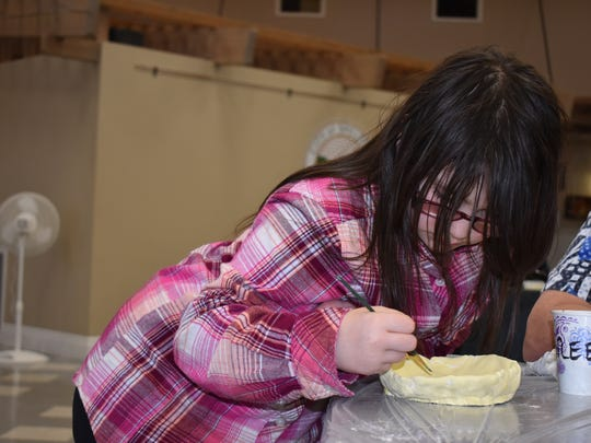 Frances Chambless, 10, a student at Pioneer Elementary, works intently on the bowl she created during the Empty Bowls fundraiser, March 14, at the Shelton Civic Center in Shelton. The Shelton Arts Commission donates all of the materials, including up to 50 pounds of clay and paint, for the event.