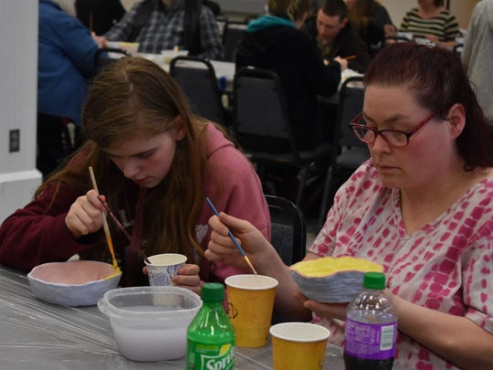 From left, Laura, 16, and Christie Chambless paint their bowls at the Shelton Arts Commission's Empty Bowls fundraiser, March 14, in Shelton. The event is a fundraiser for the Saint's Pantry Food Bank.