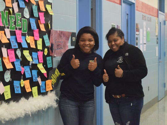 """Ashyla Robinson and Norissa Anglin give two thumbs next to the """"Take What You Need"""" board at UCHS."""