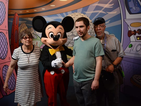 From left, Concetta Hussey, Mickey Mouse, Joey and Ed Hussey at Disney World on Nov. 5. Joey is a resident at the Anderson Center for Autism, and his progress at the center has allowed him to take a trip to Disney with his parents.