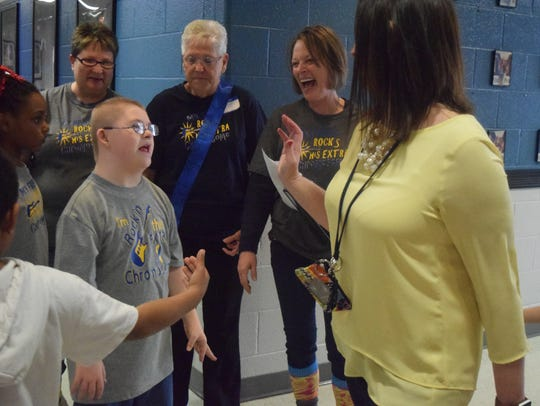 Luca Marsh pauses to high five friends and staff at