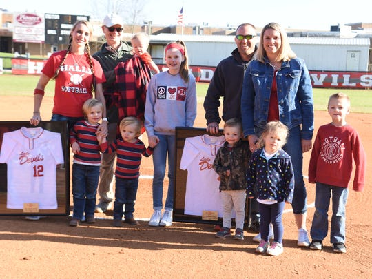 Ellisha Humphrey Frye, left in red, and Stephanie Humphrey Sayne, right in denim, were honored prior to the Halls High softball game on Thursday, March 22. They are surrounded by their family, including Eason Frye, Cael Frye, Schuler Sayne, niece Raeleigh Humphrey, Syler Sayne, (back) former HHS coach George Hall (holding Elite Frye), Skylar Frye and Stephanie's husband, Shannon Sayne. Ellisha's husband, Chad Frye, was unavailable to attend due to work travels.