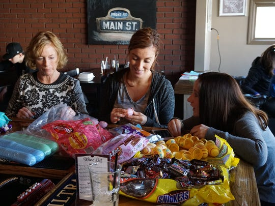From left: Mary Therese Ostanek, Joette Green, and Brittany Perry fill plastic eggs in preparation for Children's Charity of Greater Binghamton's Easter Egg Hunt.