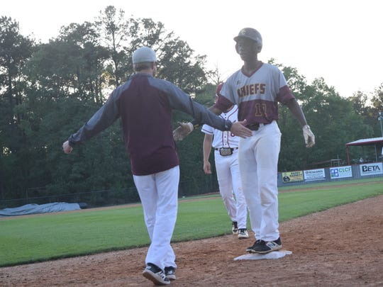 Natchitoches Central outfielder AJ Walter (12) celebrates a hit with his coach in a game against Pineville High School Friday, March 30, 2018. The Chiefs return to the playoffs for the first time in 20 years as the No. 21 seed in Class 5A.