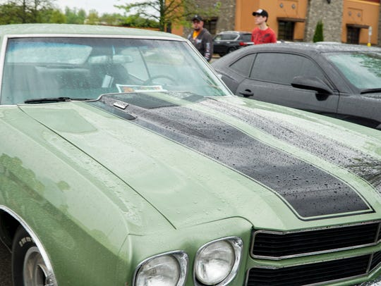 Rain falls on a vintage green Chevy Chevelle during