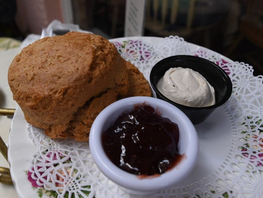 A cinnamon scone is served with honey butter and preserve