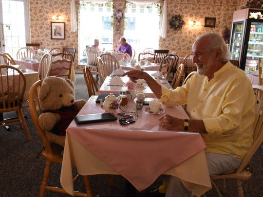 Long-time patron Don Auclair enjoys tea with Mr. Brambles, a teddy bear who is the face of Brambles English Tea Room and Gift Shop off Fifth Avenue in downtown Naples.