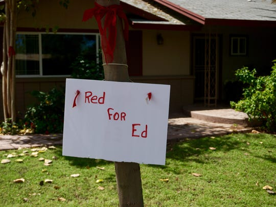 A sign and ribbon in support of #RedForEd hangs in
