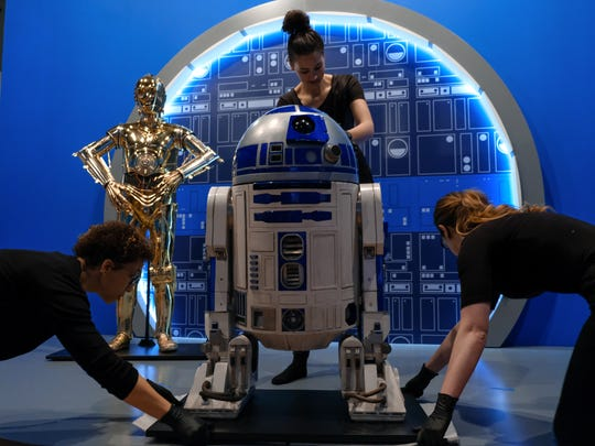 (Left to right) Museum Technicians Tracey Morton, Megan Major and Caitlin Grames work on getting R2-D2 into place C-3PO during setup for the upcoming Star Wars and the Power of Costume exhibit at the Detroit Institute of Arts on Wednesday, May 9, 2018.