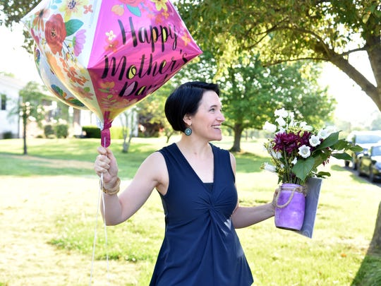 Marketing manager Heather Hebert gets ready to surprise Barbara Morris with the news that she was selected as the KNS Mom of the Year on Wednesday, May 9, 2018.