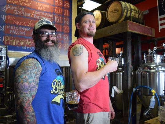 Brewers Nathan Todd and Mathew Shockley pose with their tattoos at Backshore Brewing in Ocean City.