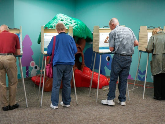 Voters fill in their ballots at a polling station in