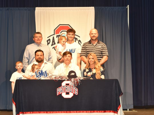 Oakland lacrosse standout Tanner Popovich recently signed with Lincoln Memorial University. Pictured in the front row (l-r) are his father, Steve Popovich holding Ryman Rose Popovich, Tanner Popovich and Brittany Popovich. In the back row (l-r) are Rowan Popovich, Oakland principal John Marshall, Stephen Popovich, holding Maddie Popovich, and athletic director Brad Cowan.