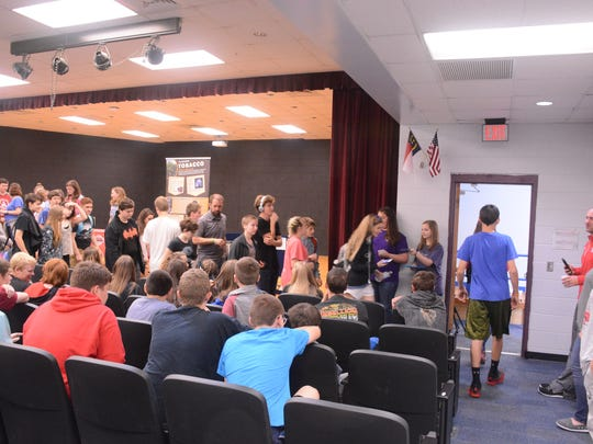MP3 club members handing out drug resource cards to 8th graders as they leave the presentation.