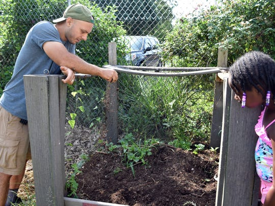 Adam Caraco, Beardsley Farm assistant director of urban agriculture, shows the compost area on the farm with camper Tiahna Hutchinson.